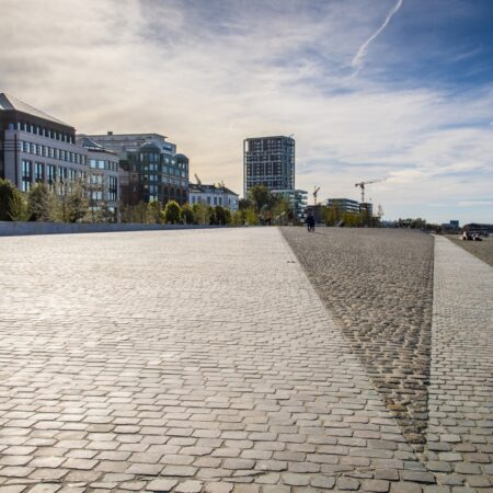Whereas the project consists of various programmes, in essence, it is divided into a green part, where park-like structures meet the street and adjacent buildings. The outstanding part of it is a paved dike that protects the city from the river when it floods. The dike is entirely designed as an open public space, built of cobblestone. A playful folding of polygons ensures a vast open space and a unique landscape experience. In times of high waters, the visitors will be able to observe the flooding of the riverbank and the consequent frolics between the river and the newly established topography.